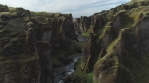 Flying through Fjadragljufur glacial canyon steep walls Iceland, sunny day, drone aerial