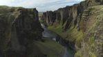 Flying through Fjadragljufur glacial canyon steep walls. Iceland, sunny day, aerial revealing shot