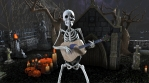 Seamless animation of a skeleton playing classic guitar in a cemetery at night. Funny halloween back