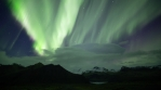 Full sky Aurora Borealis over snowy mountains and glacier, Skaftafell Iceland