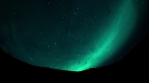 Small in space, people on a mountain ridge under Aurora glow and stars