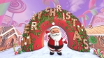 Cute Santa waving hello in a candy village. . Seamless funny Christmas animation with a doughnut wit