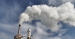 Geothermal steam billowing from pipe on Icelandic farm blue sky