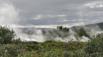 Geothermal steam rising from vent in ground Iceland summer day