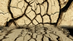 Dry land cracks falling into water