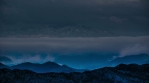 Storm clouds over high mountain peaks surreal blue valley glow time lapse 4k