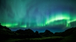 Bright aurora borealis rugged volcanic mountains Iceland realistic 4k
