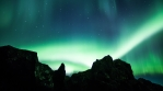 Glowing aurora borealis over volcanic rock formations time lapse 4k