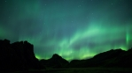 Glowing sky aurora borealis over volcanic rock formations time lapse 4k