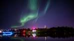 Aurora borealis over Reykjavik city bridge pond water reflection realistic 4k