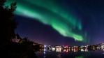 Aurora borealis over Reykjavik pond city lights water reflection realistic 4k