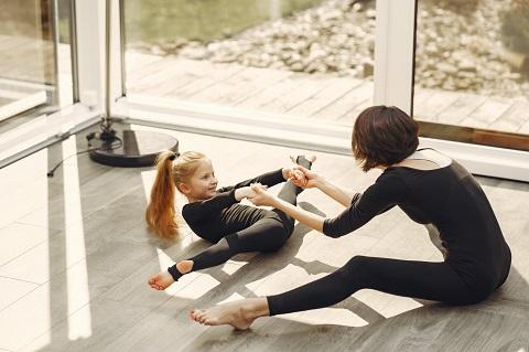 Kvinna och barn gör gymnastik tillsammans