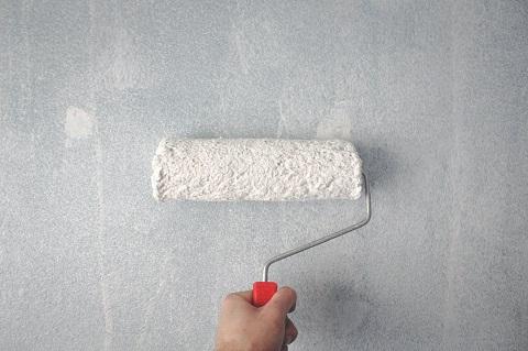 Någon målar en vägg med roller