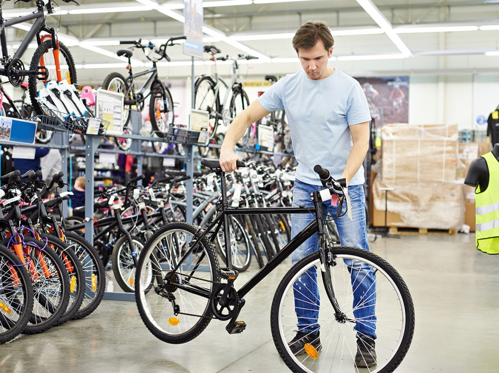 Man checks bicycle before buying in sports shop