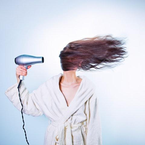 Kvinna som blåser håret