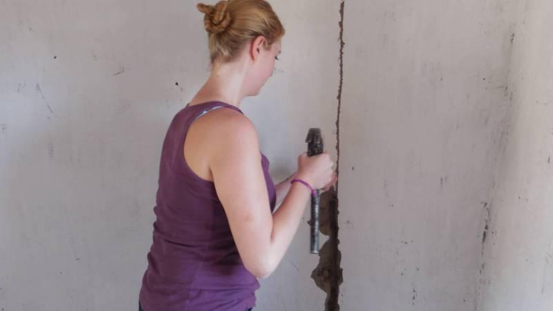 A volunteer repairing a classroom