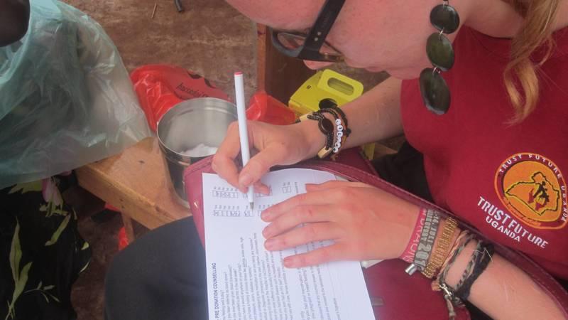 A volunteer registering people for HIV testing .