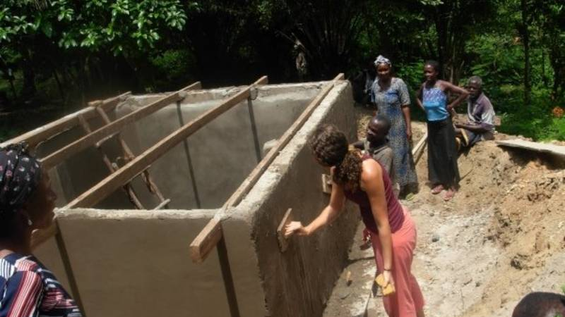 Volunteer empowering local puting up water storg