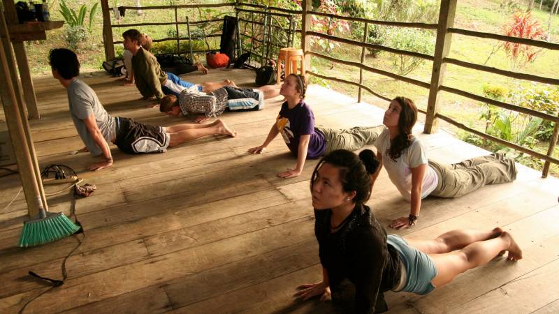 Workshop participants doing Yoga in the Comedor