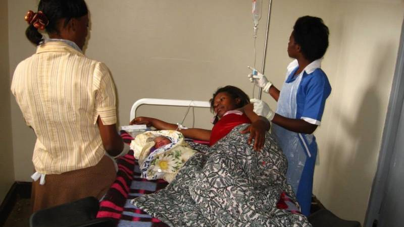 local health workers attending to a mother