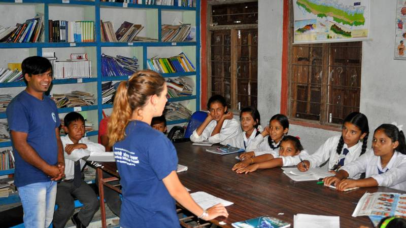 Volunteer with children while teaching