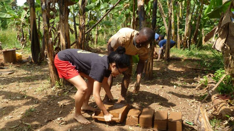 volunteer in action making bricks