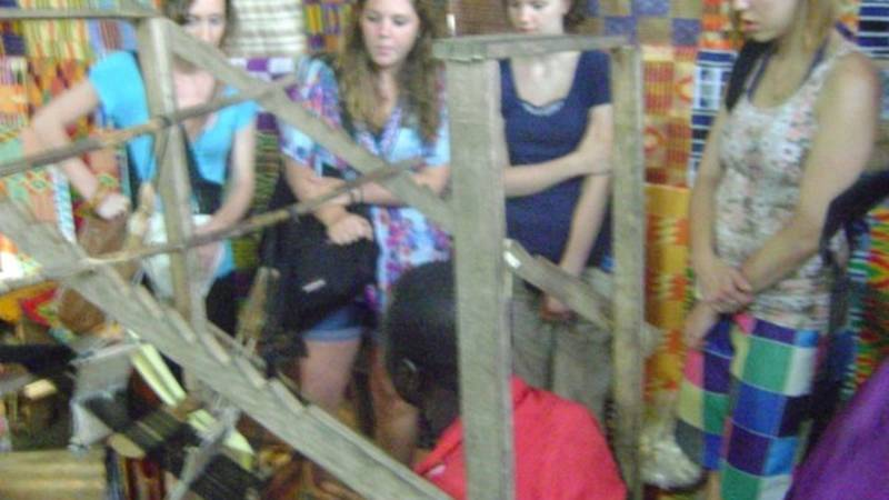 volunteers observing how to make Ghanaian clothe