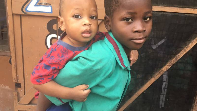 A boy is carrying his brother to the crèche