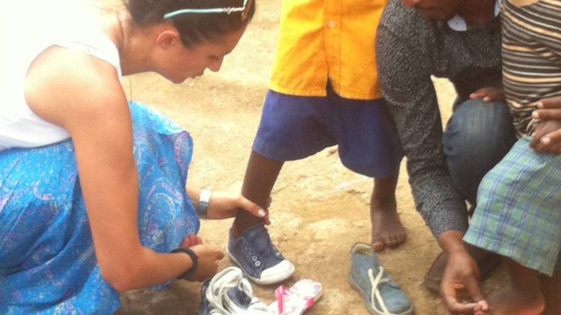 A volunteer sorting and fitting donated shoes.