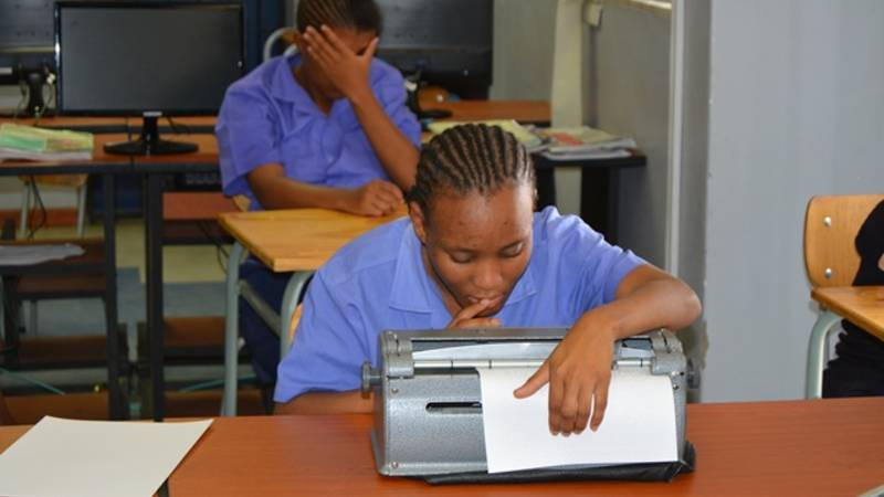 Braille learner writing exams.
