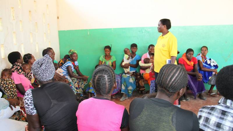 A volunteer at a meeting with community members.