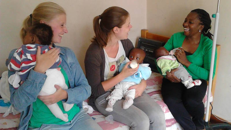 Volunteers feeding & changing children in a home