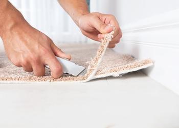 bigstock-Man-Cutting-New-Carpet-Floorin-271760068.jpg