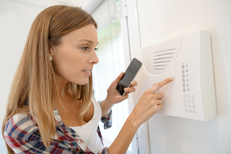 Woman-programming-home-securit-208381921.jpg