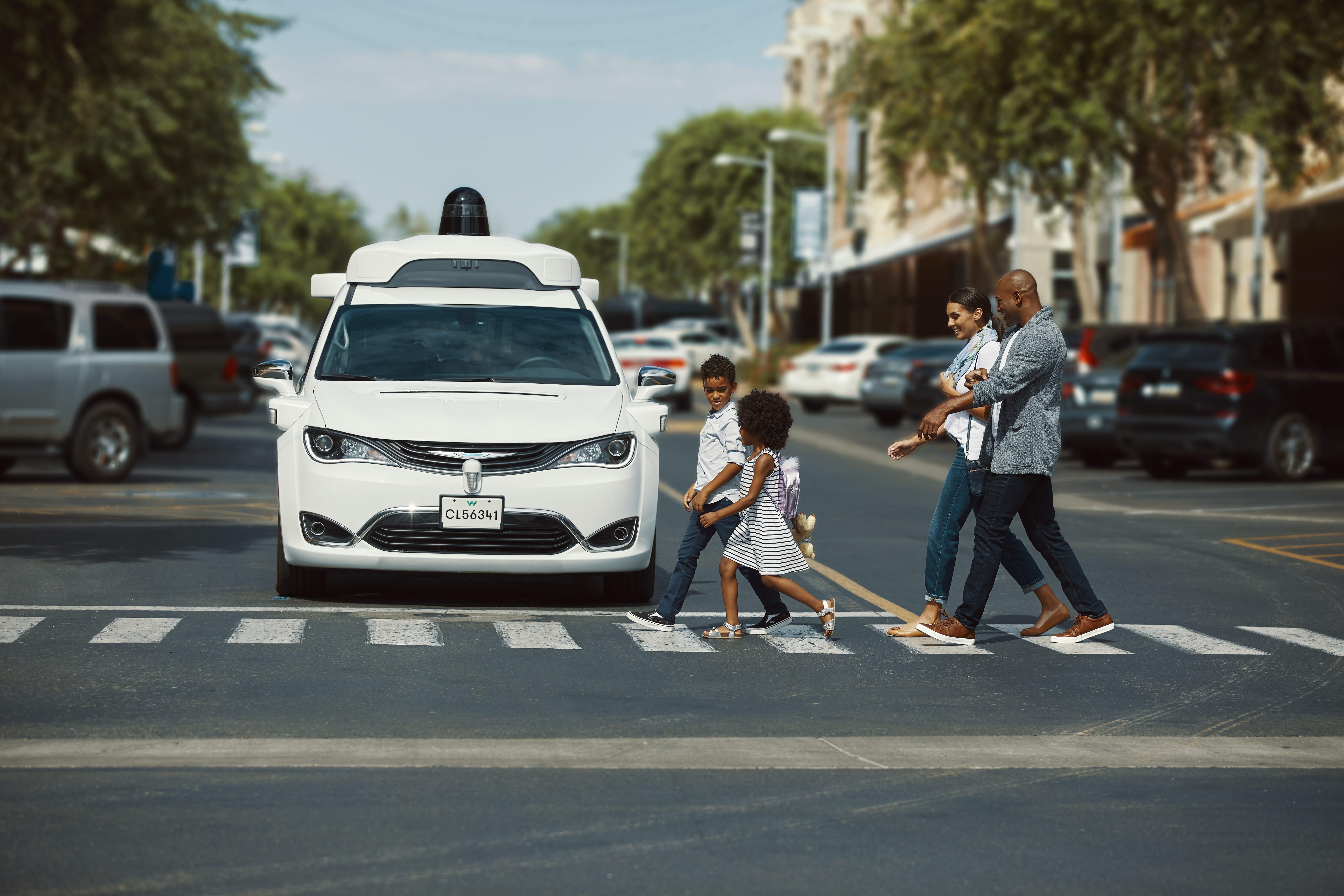Waymo's autonomously driven Chrysler Pacifica Hybrid minivan at a crosswalk