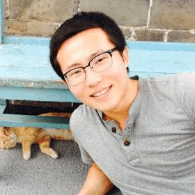tim zhang posing in front of a bench with a cat underneath it