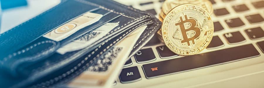 bitcoins sitting on top of a laptop and next to a wallet for online gambling