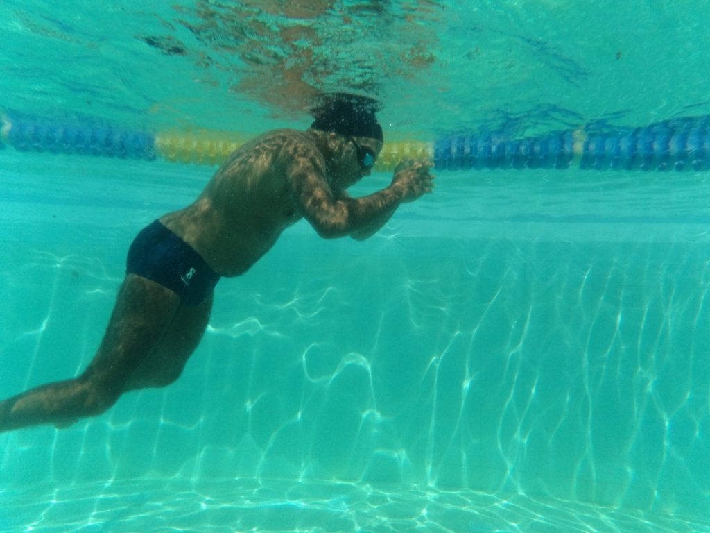 Matheus está mergulhando em uma piscina. Ele veste uma sunga, touca e óculos de natação.