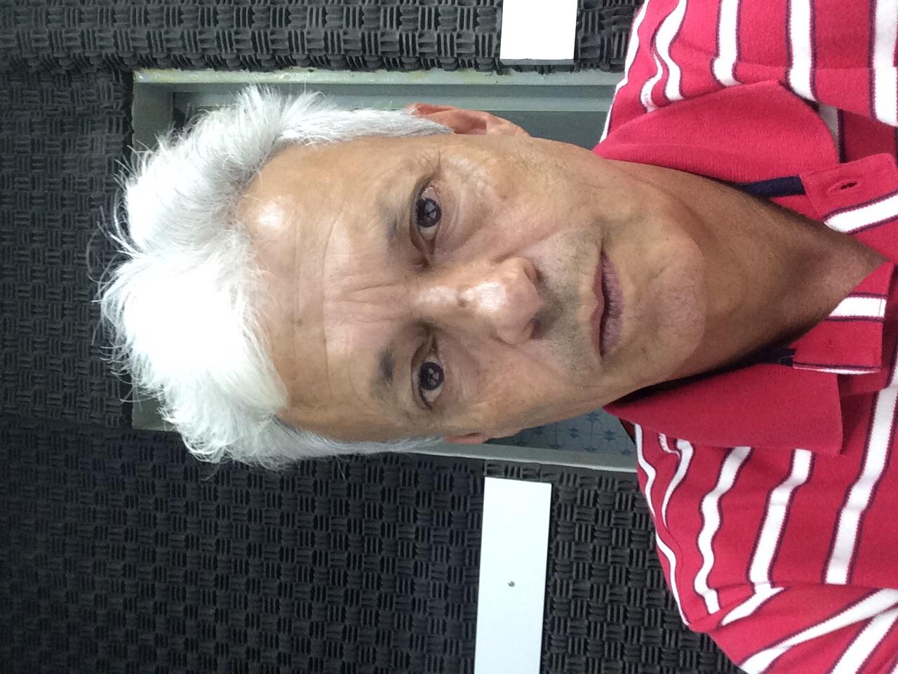 Foto de rosto, cabelos grisalhos, cor morena. Camisa com listras em horizontal nas cores vermelho e branco.
