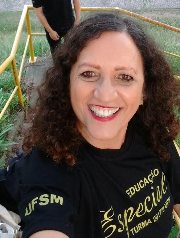 Mulher sorridente, cabelos crespos compridos, camiseta preta, dizeres Educação Especial UFSM.