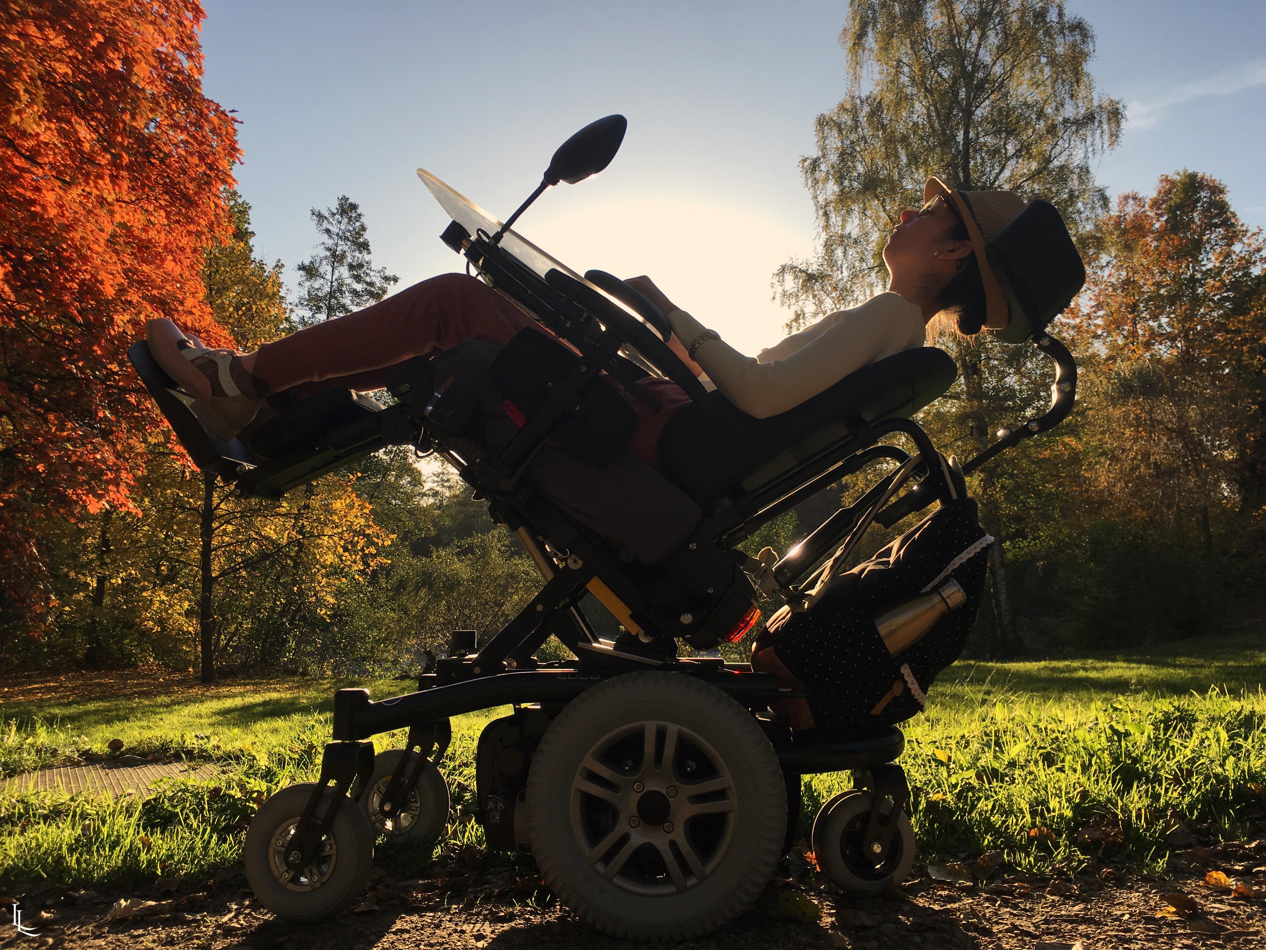 Lina está em sua cadeira de rodas. A cadeira está inclinada de forma que ela fique deitada. Ela está em um jardim, tem sol e árvores com folhas laranjas.