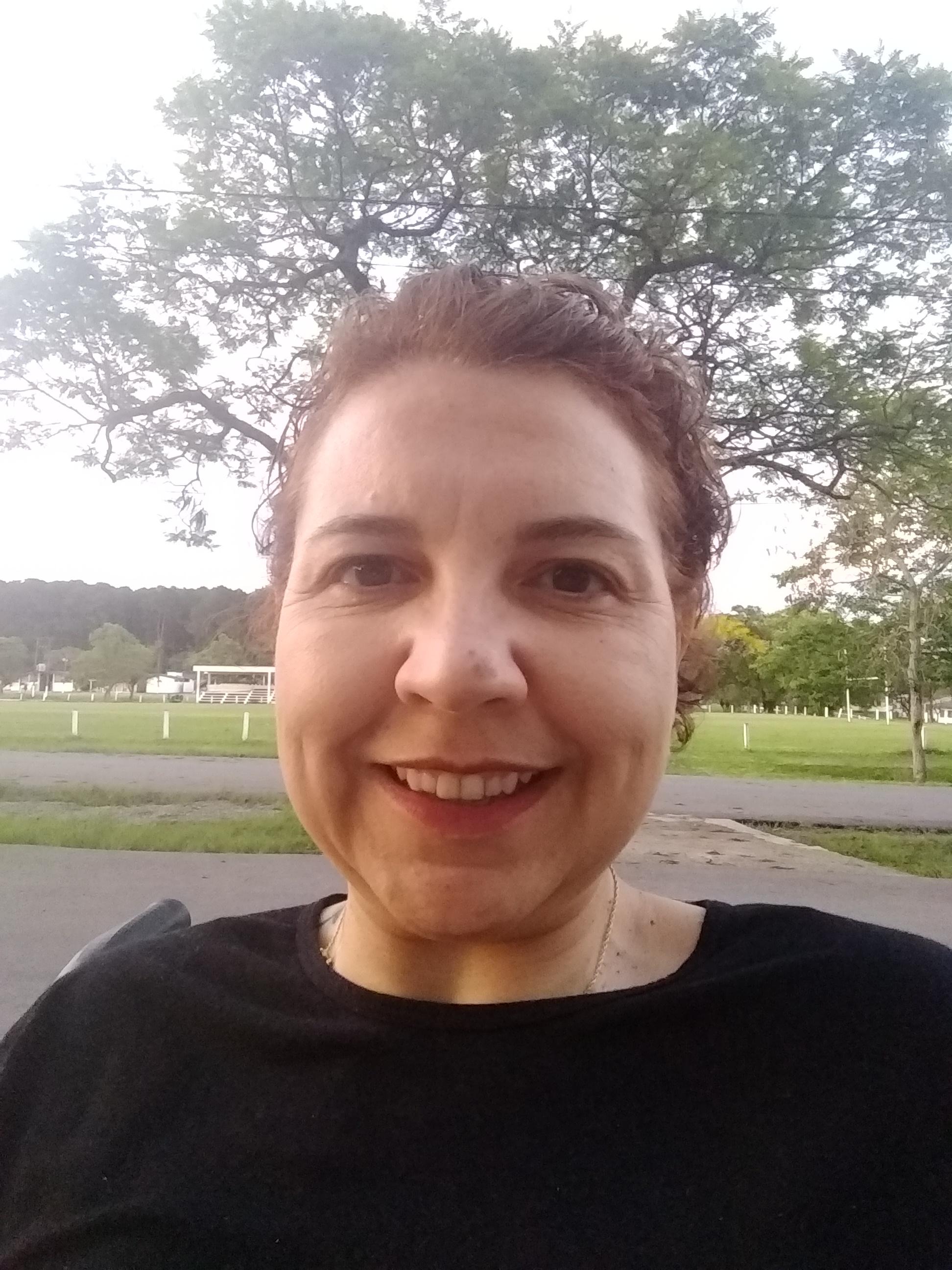 Na foto estou em um parque, sou morena clara, olhos castanhos, cabelos curtos. Estou sorrindo.