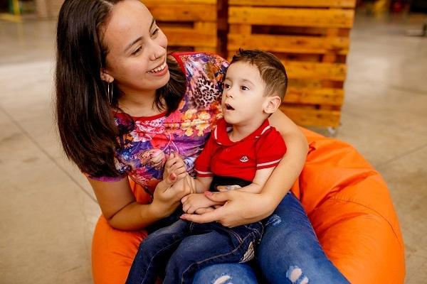 Uma mãe está com o filho no colo. Ele está usando uma Cinta para Gastrostomia.