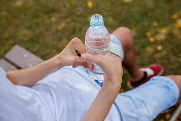 Um garoto está segurando uma garrafinha de água com auxílio de um Fixador em Alça Simples Cinza.