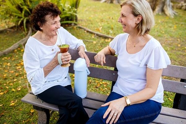 Duas mulheres, mãe e filha, estão sentadas em um banco ao ar livre, tomando chimarrão.