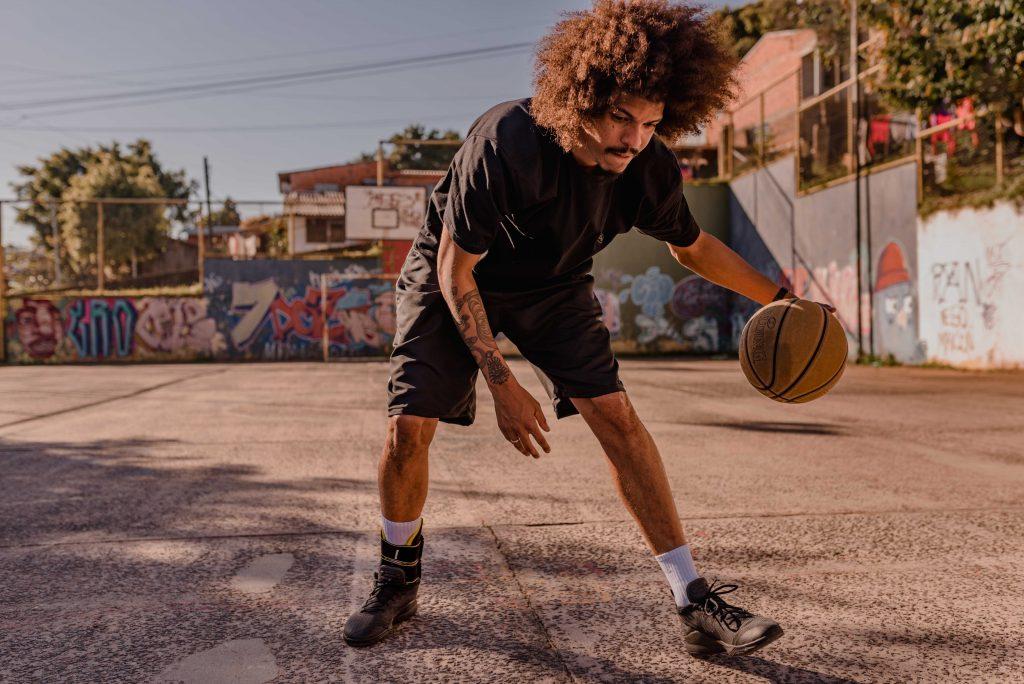 Um homem faz um movimento de basquete em que joga a bola em direção ao chão. Ele está sozinho em uma quadra ao ar livre, em um dia ensolarado.