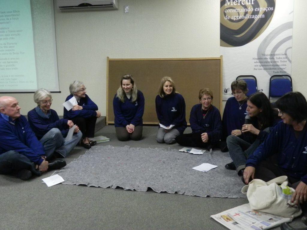 Nove pessoas em semicírculo estão sentadas no chão e conversando.