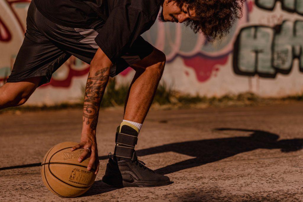 Um homem flexiona seu corpo em direção à bola de basquete que está no chão. Ele está em uma quadra ao ar livre em um dia de sol.