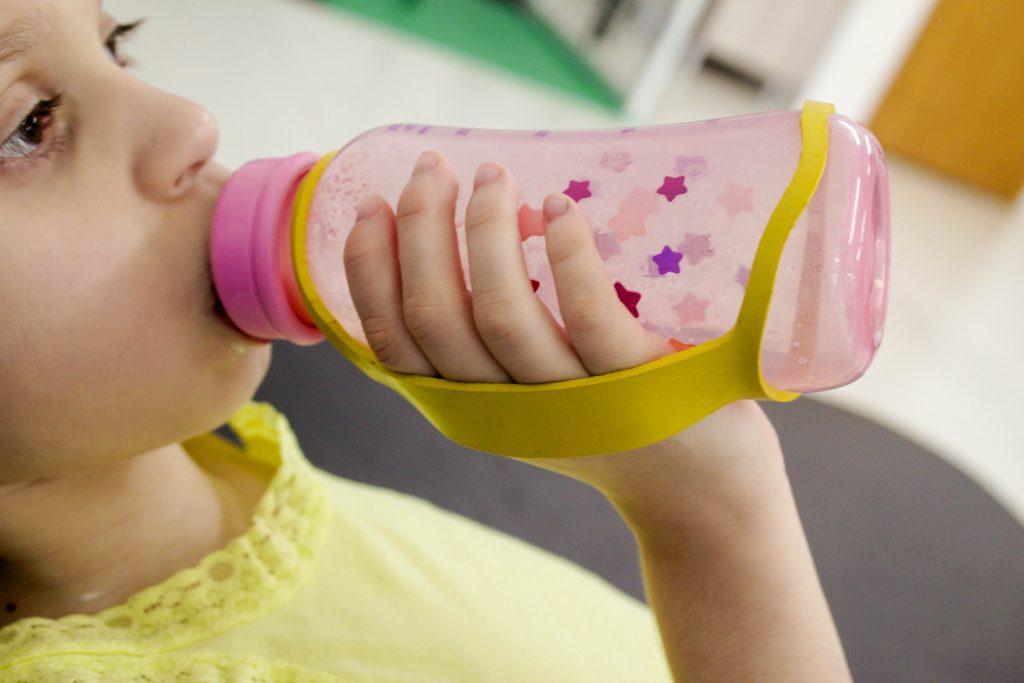 Uma criança deitada usa o fixador em alça, que é uma tira de borracha, preso a uma mamadeira e sua mão direita, para auxiliá-la a segurar o objeto.