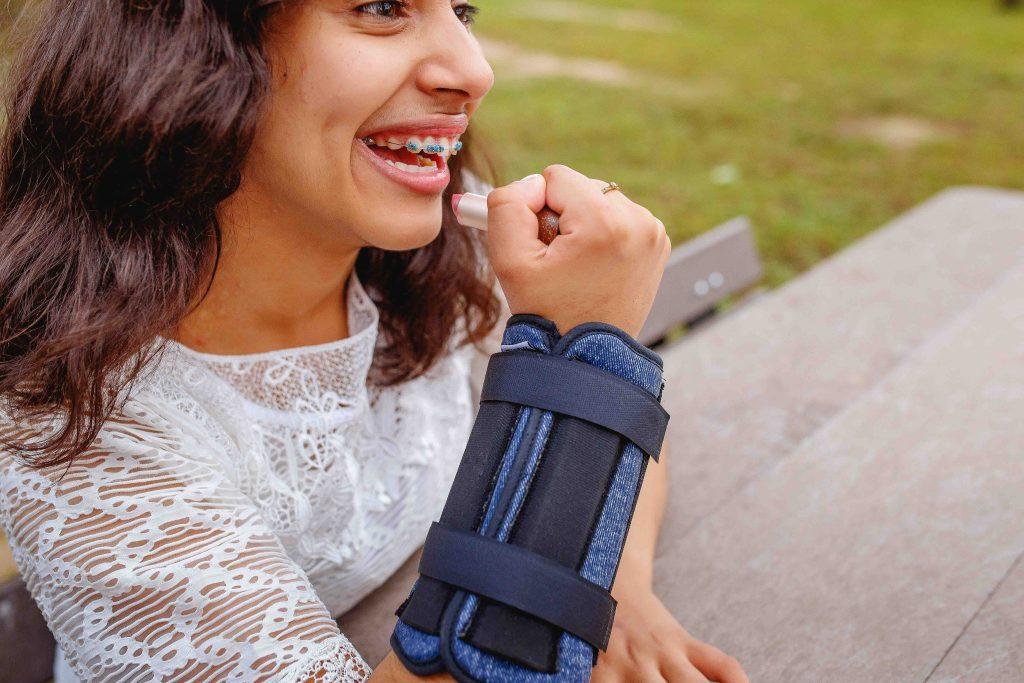 Uma mulher sentada em um ambiente externo segura um batom em sua mão direita. No pulso ela usa uma Pulseira de Peso.